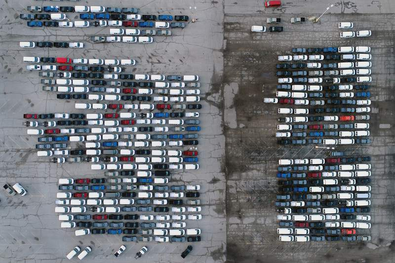 FILE - In this Wednesday, March 24, 2021 file photo, mid-sized pickup trucks and full-size vans are seen in a parking lot outside a General Motors assembly plant where they are produced in Wentzville, Mo.  General Motors says efforts to manage the global computer chip shortage have worked better than expected, so its financial results will improve over previous forecasts. The company says in a statement Thursday, June 3,  it has made engineering changes, prioritized semiconductor use and pulled some potential deliveries into the second quarter. (AP Photo/Jeff Roberson, File)