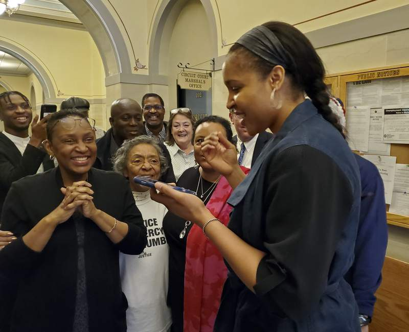 Jefferson City, Mo., native and WNBA star Maya Moore, right, calls Jonathan Irons as supporters react Monday, March 9, 2020, in Jefferson City after Cole County Judge Dan Green overturned Irons' convictions in a 1997 burglary and assault case. Moore, a family friend, had supported Irons, sharing his story on a national basis. (Jeff Haldiman/The Jefferson City News-Tribune via AP)