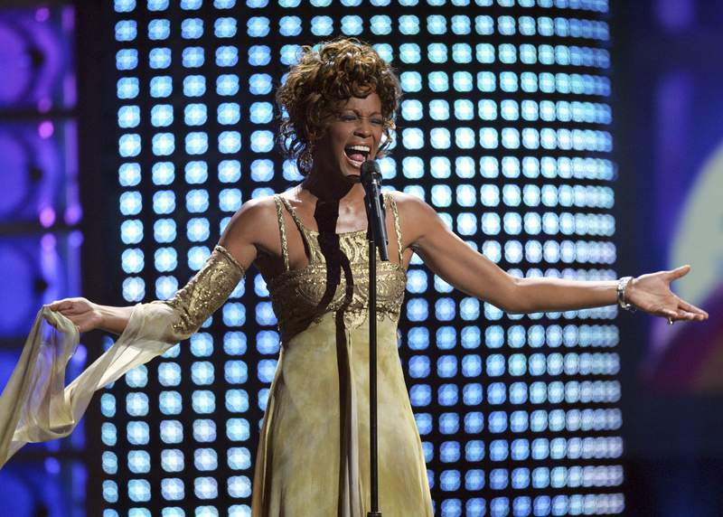 "FILE - In this Sept. 15, 2004 file photo, recording artist Whitney Houston performs at the 2004 World Music Awards at the Thomas and Mack Arena in Las Vegas. Houston is about to appear on the concert stage again. Eight years after her death, five years after the show was conceived and a year after production began, a holographic Houston will embark on a European tour starting Feb. 25, with U.S. dates expected to follow. The singer's sister-in-law and former manager Pat Houston says it's the right time for a revival, and says it's a show Whitney Houston would've wanted. The concerts will feature a projected Houston performing most of her biggest hits, including I Will Always Love You,"" with real backup dancers and a live band. (AP Photo/Eric Jamison, file)"