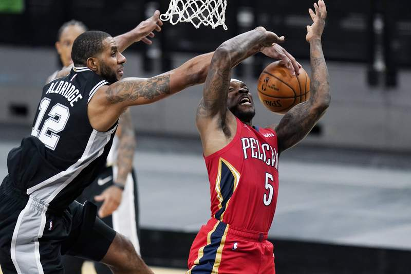 New Orleans Pelicans guard Eric Bledsoe (5) is blocked by San Antonio Spurs center LaMarcus Aldridge (12) as he tries to score during the first half of an NBA basketball game in San Antonio, Saturday, Feb. 27, 2021. (AP Photo/Eric Gay)