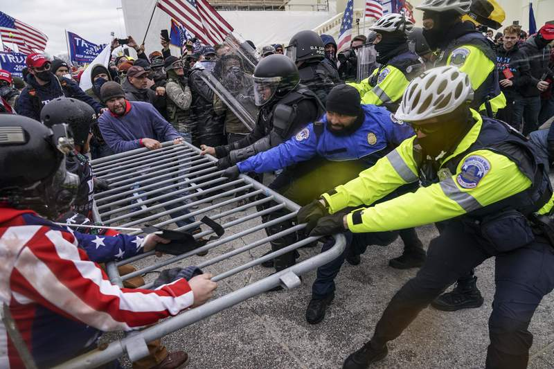 FILE - In this Jan. 6, 2021, file photo a violent mob of Trump supporters try to break through a police barrier at the Capitol in Washington. Violent extremists motivated by political grievances and racial biases pose an elevated threat to the U.S. homeland, officials said Wednesday, March 17, in a unclassified intelligence report released more than two months after a violent mob of insurrectionists stormed the U.S. Capitol. (AP Photo/John Minchillo File)