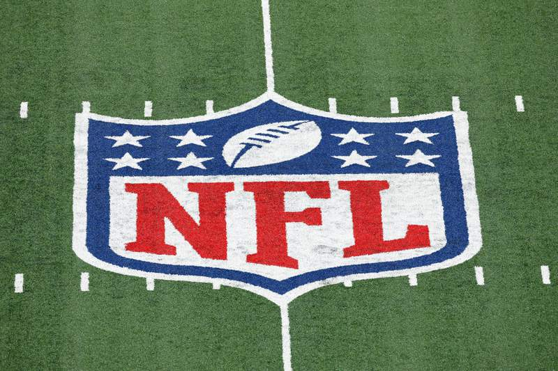 FILE - In this Nov. 2, 2020, file photo,  the NFL logo is displayed  at midfield during an NFL football game between the Tampa Bay Buccaneers and the New York Giants in East Rutherford, N.J. There are some very rich people about to get a whole lot richer. Who else but NFL owners? Probably within the next week, those 32 multi-millionaires/billionaires will see their future earnings increase exponentially. The league is on the verge of extending its broadcast deals with its current partners, and with a new full-time rights holder in Amazon likely acquiring streaming rights. (AP Photo/Adam Hunger, FIle)