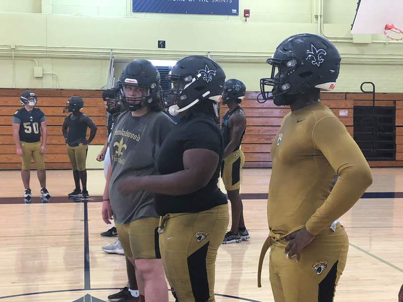 Sandalwood football players practice in the gym on a rainy Monday afternoon. Fall sports practices began Monday around the state.