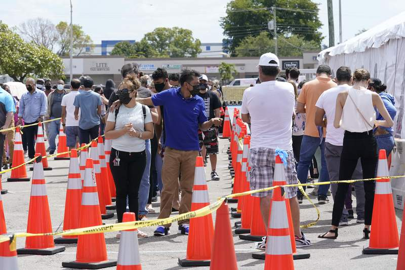 People wait in line to receive a COVID-19 vaccine at a FEMA vaccination center at Miami Dade College, Monday, April 5, 2021, in Miami. (AP Photo/Lynne Sladky)