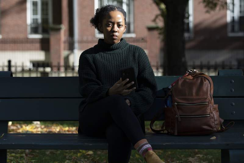 Harvard University graduate student Maya James poses in a park near the university, Wednesday, Oct. 14, 2020, in Cambridge, Mass. Law enforcement and voting advocates are warning that con artists are exploiting the election with scams targeting voters. James received an email from a political action committee that seemed harmless: if you support Joe Biden, it urged, click here to check you're registered to vote. Instead, she Googled the name of the group and it didnt exist - a clue the email was a phishing scam. (AP Photo/Michael Dwyer)