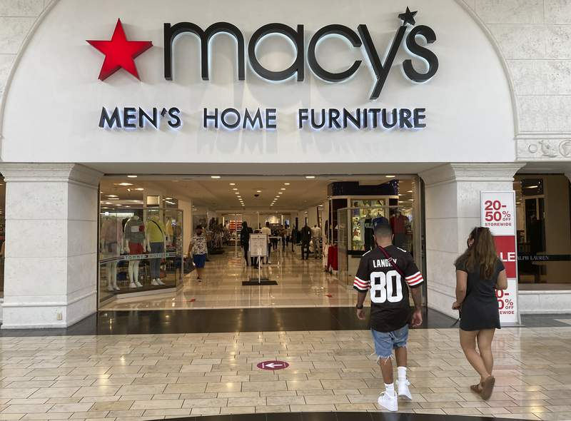 Shoppers walk into a Macy's department store Monday, Feb. 22, 2021, at Miami International Mall in Doral, Fla. Macys is reporting a 52% drop in fiscal-fourth quarter earnings while sales dropped nearly 19% as shoppers continue to stay away from many physical stores during the pandemic. The department store chain said Tuesday, Feb. 23 it anticipates 2021 as a recovery and rebuilding year as the company sets a foundation for growth. (AP Photo/Wilfredo Lee)