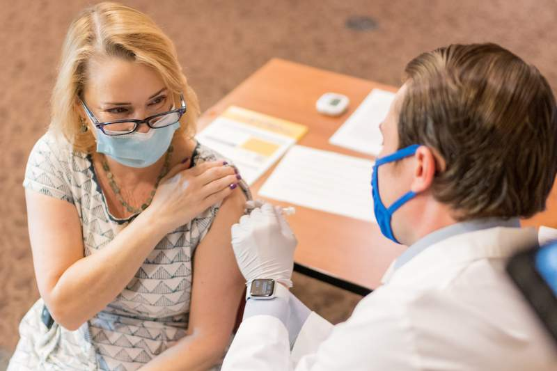 UF Health Pharmacist Clayton Johnston administers the 2nd dose of the Pfizer Covid-19 vaccine to Nicole Iovine, lead Epidemiologist in the Division of Infectious Diseases and Global Medicine at UF Health.
