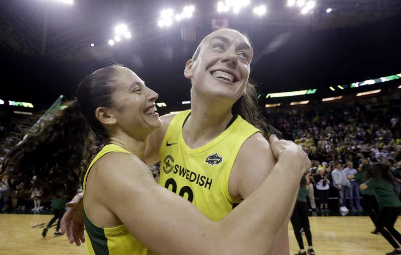 FILE - This Sept. 4, 2018, file photo shows Seattle Storm's Sue Bird, left, and Breanna Stewart embracing after the Storm defeated the Phoenix Mercury 94-84 during Game 5 of a WNBA basketball playoff semifinal, in Seattle. With Breanna Stewart and Sue Bird back, the Seattle Storm are healthy to begin the season and sit atop the preseason Associated Press WNBA poll. The Storm were the unanimous choice receiving all 16 first-place votes from the national media panel Tuesday, July 21, 2020. (AP Photo/Elaine Thompson, File)