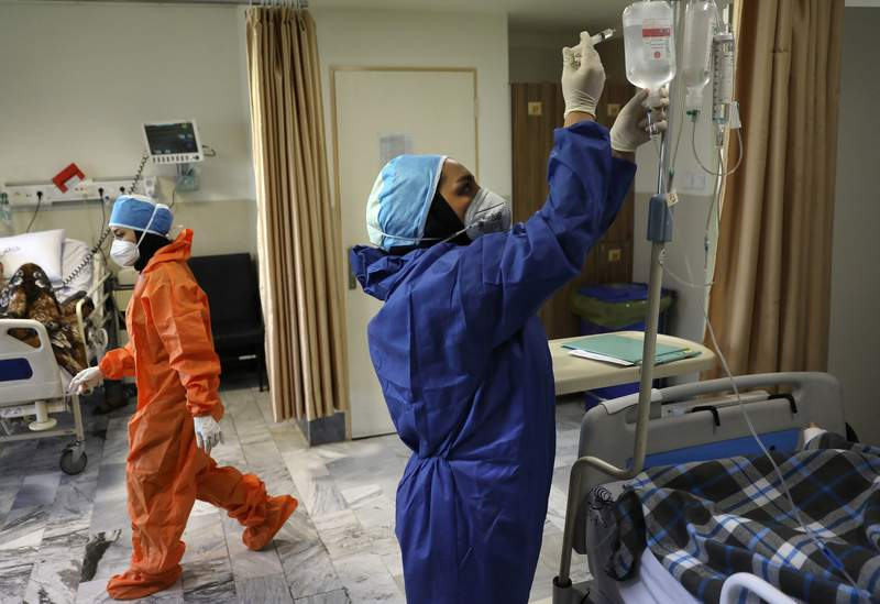 FILE - In this June 16, 2020, file photo, nurses tend to COVID-19 patients at the Shohadaye Tajrish Hospital in Tehran, Iran. Iran surpassed 20,000 confirmed deaths from the coronavirus on Wednesday, Aug. 19, 2020, the health ministry said, the highest death toll for any Middle East country so far in the pandemic. (AP Photo/Vahid Salemi, File)