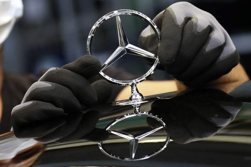 FILE - In this Thursday, April 30, 2020 file photo, an employee attaches a Mercedes emblem as he works on a Mercedes-Benz S-class car at the Mercedes plant in Sindelfingen, Germany. German automaker Daimler said it will split itself into two independent companies by spinning off its truck and bus division. The Stuttgart-headquartered company said Wednesday, Feb. 3, 2021 that a significant majority stake in the truck business would be distributed to current shareholders, and that Daimler would at the appropriate time be renamed Mercedes-Benz, the brand name under which it sells luxury cars.  (AP Photo/Matthias Schrader, file)