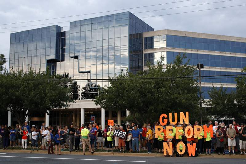 FILE - In this Aug. 5, 2019, file photo, people gather at a vigil for recent victims of gun violence outside the National Rifle Association's headquarters building in Fairfax, Va. The NRA has been embroiled in a legal and financial battle that liberals have cheered as the potential downfall of the powerful gun rights lobby, opening up a wide path for reform. Not so fast. While the battle over gun rights is shifting from Washington to the states, the NRAs message has become so solidified in the Republican political fabric that its self-sustaining, even if the gun rights organization that led the way ceases to exist, leaders on both sides say. (AP Photo/Patrick Semansky, File)