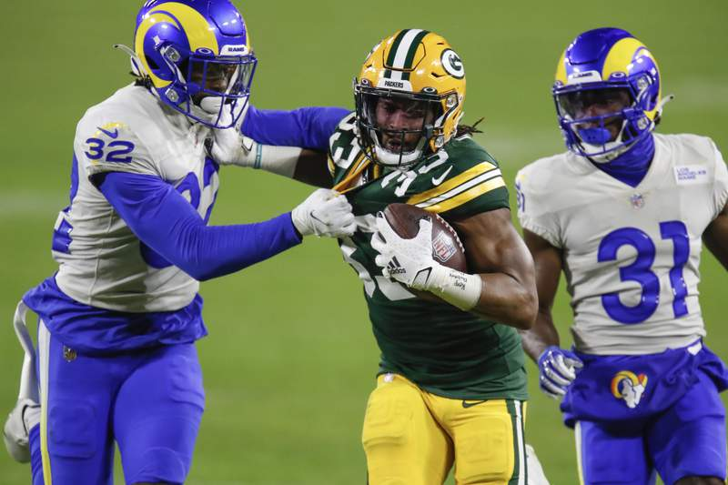 File-This Jan. 16, 2021, file photo shows Green Bay Packers' Aaron Jones (33) being chased down by Los Angeles Rams' Jordan Fuller (32) and Rams' Darious Williams during the second half of an NFL divisional playoff football game in Green Bay, Wis. The Pro Bowl running back, Jones has agreed to a new deal with the Green Bay Packers and wont be exploring free agency. Drew Rosenhaus, Jones agent, confirmed that his client had agreed on a four-year deal worth $48 million that includes a $13 million signing bonus. (AP Photo/Matt Ludtke, File)