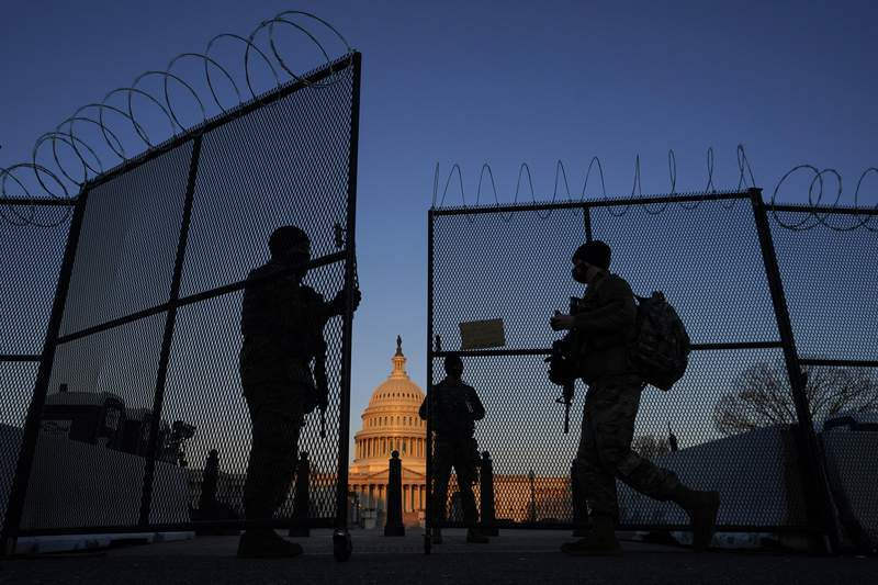 National Guard soldiers open a gate of the razor wire-topped perimeter fence around the Capitol to allow a colleague in at sunrise in Washington, Monday, March 8, 2021. (AP Photo/Carolyn Kaster)