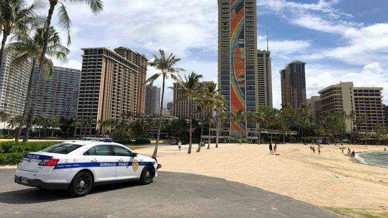 A police officer arrives to tell people to leave Waikiki Beach in Honolulu on Saturday, March 28. Like many cities across the world, Honolulu came to an eerie standstill as the coronavirus pandemic spread throughout the islands.