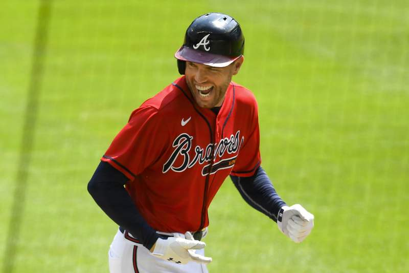 FILE - Atlanta Braves' Freddie Freeman reacts as he runs along the third base line after hitting a grand slam home run in the sixth inning of a baseball game against the Washington Nationals in Atlanta, in this Sunday, Sept. 6, 2020, file photo. NL MVP Freddie Freeman has followed his big season with the Atlanta Braves with an even more memorable offseason. He and his wife have two baby boys, including one from a surrogate mother. He calls his new babies his twins with a twist.(AP Photo/John Amis, File)