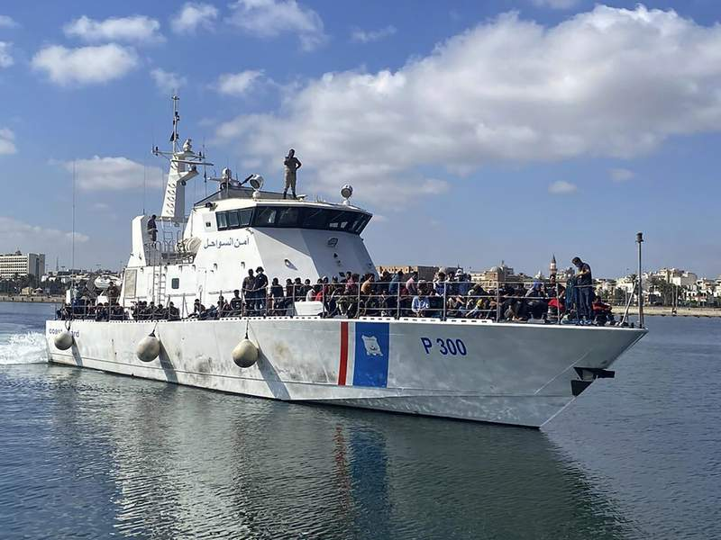 This photo provided by the International Organization for Migration shows migrants from four boats being returned to the shore in Tripoli, Libya, Wednesday, July 21, 2021. Libya's coast guard intercepted Wednesday four boats in the Mediterranean Sea carrying migrants trying to reach Europe, a U.N. official said. According to the migrants, 20 people from one of the vessels had gone overboard earlier in the day and were presumed to have drowned. (International Organization for Migration, via AP)