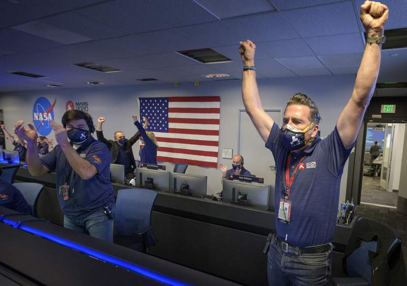 In this photo provided by NASA, members of NASA's Perseverance rover team react in mission control after receiving confirmation the spacecraft successfully touched down on Mars, Thursday, Feb. 18, 2021, at NASA's Jet Propulsion Laboratory in Pasadena, Calif. The landing of the six-wheeled vehicle marks the third visit to Mars in just over a week. Two spacecraft from the United Arab Emirates and China swung into orbit around the planet on successive days last week. (Bill Ingalls/NASA via AP)