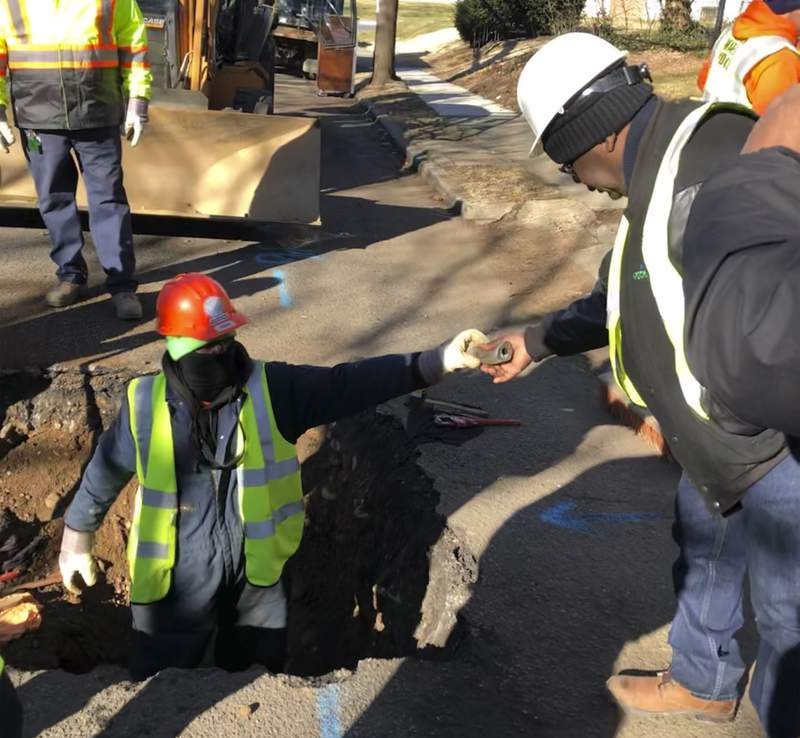 A worker hands a piece of lead pipe to a colleague as they work to remove water service lines Thursday, Jan. 9, 2020, in Trenton, N.J. The city announced it is replacing 37,000 lead pipes over five years as part of an an effort to remove the potentially harmful pipes. (AP Photo/Mike Catalini)