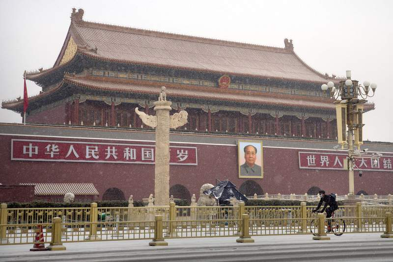 A man wears a face mask as he rides a bicycle past Tiananmen Gate near Tiananmen Square during a snowfall in Beijing, Wednesday, Feb. 5, 2020. Deaths from a new virus rose to 490 in mainland China on Wednesday while new cases on a Japanese cruise ship, in Hong Kong and in other places showed the increasing spread of the outbreak and renewed attention toward containing it. (AP Photo/Mark Schiefelbein)