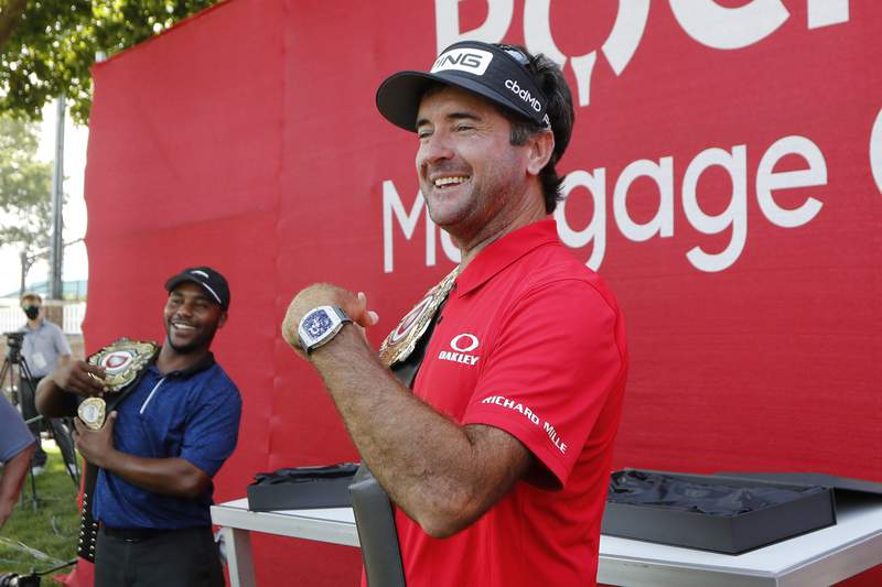 Bubba Watson and Harold Varner III, left, show off the winner's belts after their win in a nine-hole exhibition at the Detroit Golf Club in Detroit.