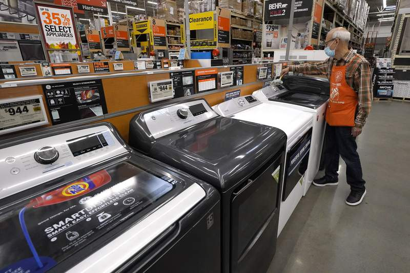 FILE - In this Oct. 29, 2020 file photo, worker Javad Memarzadeh, of Needham, Mass., right, dusts washers on a display, at a Home Depot location, in Boston. Orders for big-ticket manufactured goods rebounded 0.5% in March as U.S. factories recovered from frigid February weather disruptions.  (AP Photo/Steven Senne, File)