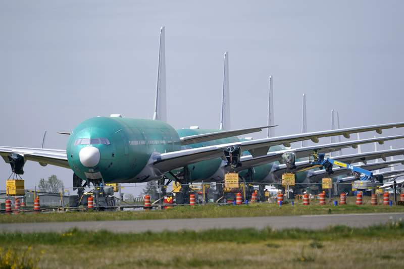 A line of Boeing 777X jets are parked nose to tail on an unused runway at Paine Field, near Boeing's massive production facility, Friday, April 23, 2021, in Everett, Wash.  Boeing Co. on Wednesday, April 28,  reported a loss of $537 million in its first quarter. The Chicago-based company said it had a loss of 92 cents per share. Losses, adjusted for non-recurring gains, were $1.53 per share.  (AP Photo/Elaine Thompson)