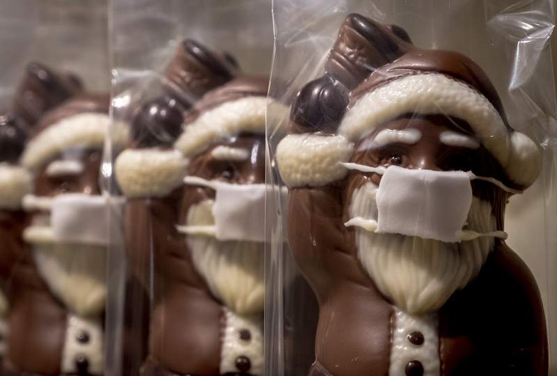 A confectioner offers chocolate Santa Claus wearing a face mask, displayed in the window of a shop in central Frankfurt, Germany, Sunday, Nov. 22, 2020. (AP Photo/Michael Probst)
