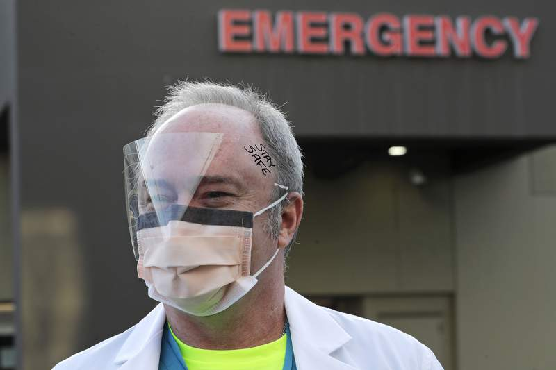 Dr. Stephen Anderson, a physician who works in the Emergency Department at the MultiCare Auburn Medical Center in Auburn, Wash., wears a mask and face shield as he poses for a photo before starting his shift. (Photo by Ted S. Warren)