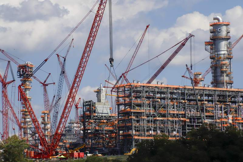 FILE This file photo from Oct. 3, 2019 shows cranes as they work on construction of the Shell Pennsylvania Petrochemicals Complex and ethylene cracker plant located in Potter Township, Pa. Under mounting pressure from state and local officials, Shell announced it is suspending construction at its massive manufacturing complex in western Pennsylvania. The company said Wednesday, March, 18, 2020 that it's temporarily halting work at its soon-to-be-completed plant which will turn the area's vast natural gas deposits into plastics. The shutdown takes effect immediately. (AP Photo/Keith Srakocic, File)