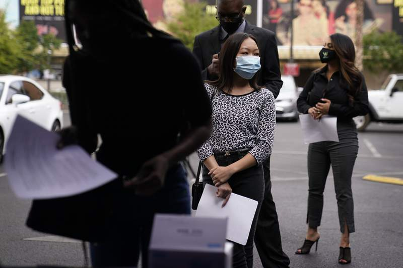 People wait in line, resumes in hand, while waiting to apply for jobs during an outdoor hiring event for the Circa resort and casino, Tuesday, April 27, 2021, in Las Vegas.  The number of Americans applying for unemployment benefits dropped by 13,000 last week to 553,000, the lowest level since the pandemic hit last March and another sign the economy is recovering from the coronavirus recession.  (AP Photo/John Locher)