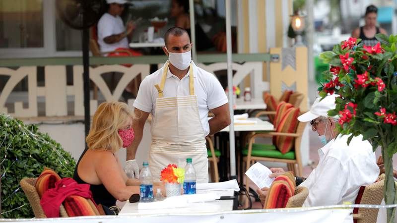 Jeffrey Holinka wears a protective face mask as he waits to receive an order at the On Ocean 7 Cafe along Ocean Drive in Miami Beach in late May. Ocean Drive was closed to traffic as restaurants in Miami Beach reopened after being closed to mitigate the spread of the coronavirus.