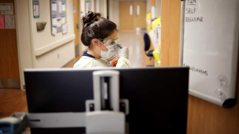 Nurses a COVID-19 unit check the fit of protective equipment before entering a patient's room.