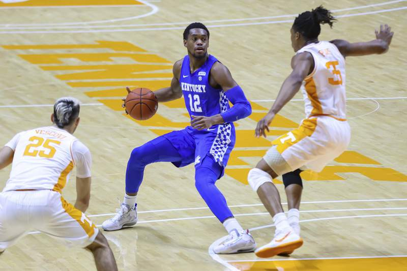 Kentucky's Keion Brooks Jr. (12) brings the ball up court against Tennessee's Yves Pons (35) during an NCAA college basketball game Saturday, Feb. 20, 2021, in Knoxville, Tenn. (Randy Sartin/Pool Photo via AP)