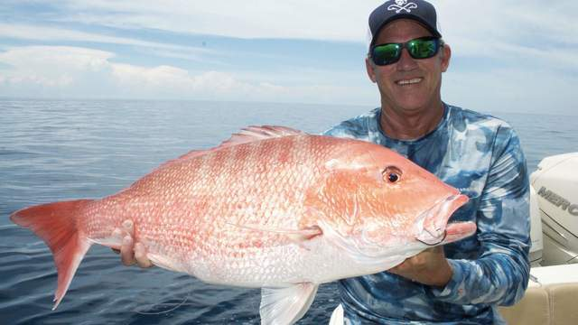 Capt Don Dingman of Hook The Future TV shows off a red snapper before releasing it back into the Atlantic.