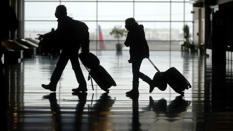 FILE - In this Tuesday, March 9, 2021 file photo, travelers walk through the Salt Lake City International Airport, in Salt Lake City. The number of people flying in the United States has eclipsed the year-ago level for the first time in the pandemic period, although travel remains deeply depressed from 2019. The Transportation Security Administration said 1.34 million people passed through U.S. airport checkpoints on Sunday, March 14 topping the 1.26 million people that TSA screened on the comparable Sunday a year ago.  (AP Photo/Rick Bowmer, File)