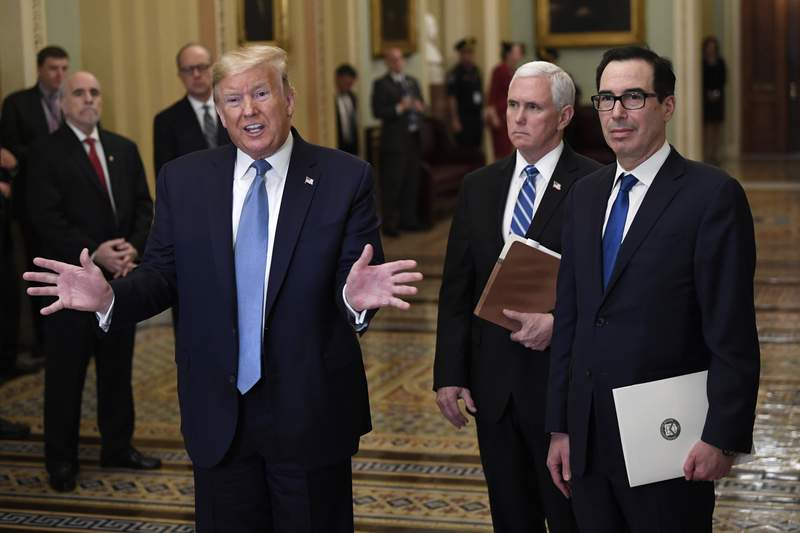 President Donald Trump, left, standing with Vice President Mike Pence and Treasury Secretary Steven Mnuchin, right, talks to reporters about the coronavirus outbreak on Tuesday, March 10, 2020, on Capitol Hill in Washington. (AP Photo/Susan Walsh)