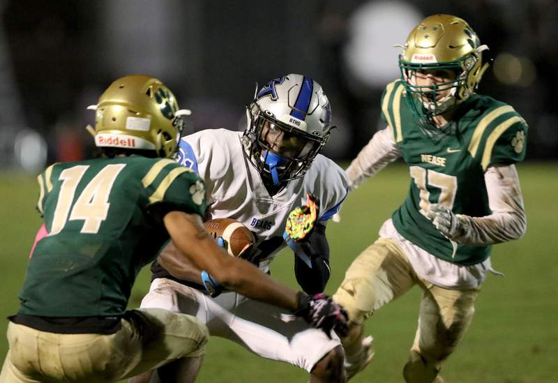 Bartram running back Eric Weatherly, center, runs from Nease defensive backs Jordan Wilhite, left, and Creed McClafferty, Friday October 16, 2020.