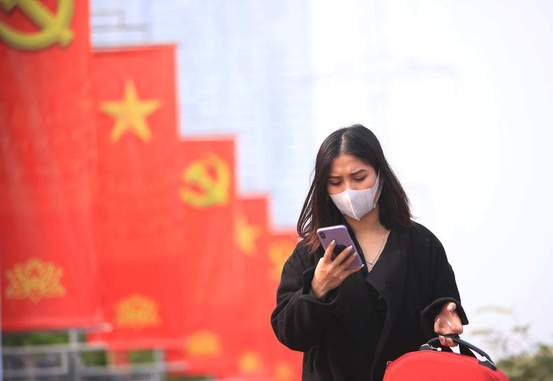 FILE - In this Jan. 23, 2021 file photo, a woman wearing face mask looks at her phone in Hanoi, Vietnam.  Vietnam says it has discovered a new coronavirus variant thats a hybrid of strains first found in India and the U.K. The Vietnamese health minister made the announcement Saturday, May 29.   (AP Photo/Hau Dinh, File)