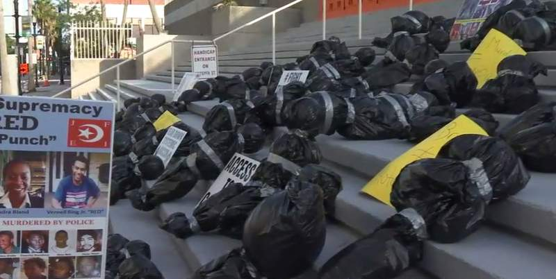 Demonstrators set up body bags on the steps to JSO headquarters