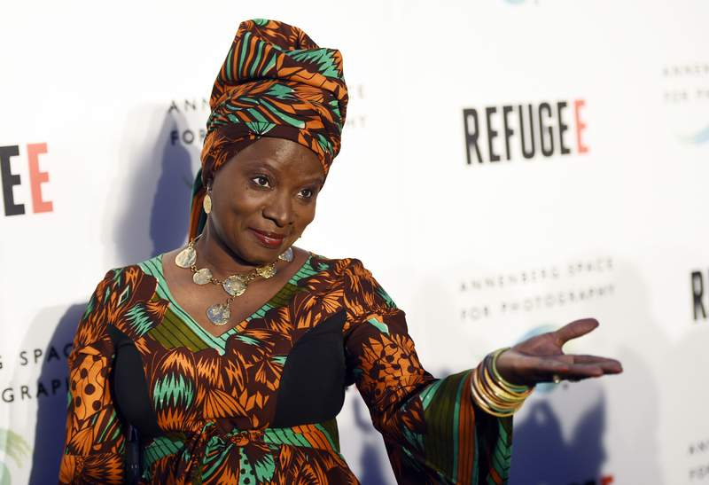 """FILE - In this Thursday, April 21, 2016, file photo, singer and UNICEF Goodwill Ambassador Angelique Kidjo poses at the opening of the new photography exhibit """"REFUGEE"""" at The Annenberg Space for Photography in Los Angeles. Kidjo uses her artistry and her activism to connect beyond language and skin color. Kidjo and other international musicians are performing social justice anthems for an online fundraising concert called Peace Through Music: A Global Event for Social Justice. (Photo by Chris Pizzello/Invision/AP, File)"""