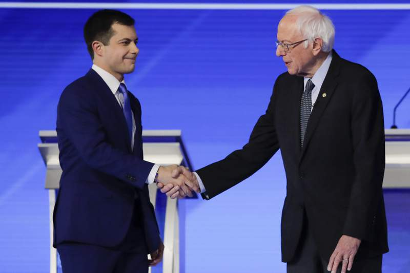Democratic presidential candidates former South Bend Mayor Pete Buttigieg and Sen. Bernie Sanders, I-Vt., shake hands on stage Friday, Feb. 7, 2020, before the start of a Democratic presidential primary debate hosted by ABC News, Apple News, and WMUR-TV at Saint Anselm College in Manchester, N.H. (AP Photo/Charles Krupa)