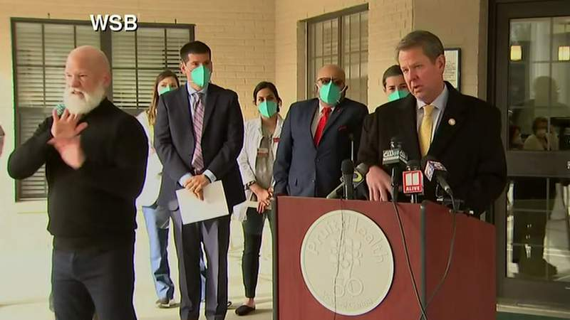 Gov. Brian Kemp and other state officials speak Monday at Pruitt Health Facility in Gainesville, Georgia.