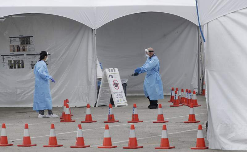 Healthcare workers organize an area at a newly opened drive-through COVID-19 testing site at the Miami-Dade County Youth Fair & Exposition center, Wednesday, April 8, 2020, in Miami. (AP Photo/Wilfredo Lee)