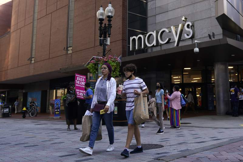 FILE - In this July 14, 2021 file photo, pedestrians pass the Macy's store in the Downtown Crossing shopping area, in Boston.   Americans cut back on their spending last month as a surge in COVID-19 cases kept people away from stores. Retail sales fell a seasonal adjusted 1.1% in July from the month before, the U.S. Commerce Department said Tuesday, Aug. 17.   (AP Photo/Charles Krupa, File)