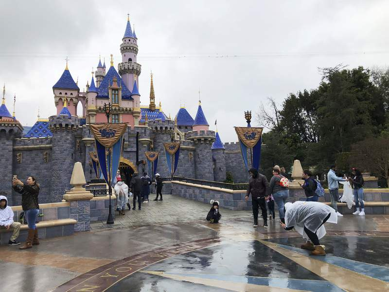 FILE - In this March 13, 2020 file photo, visitors take photos at Disneyland in Anaheim, Calif., the last day the park was open due to the COVID-19 pandemic. Theme park industry leaders in California say they aren't pleased with proposed reopening guidance being considered by Gov. Gavin Newsom's administration. Erin Guerrero, executive director of the California Attractions and Parks Association, said amusement park leaders wanted changes to a draft they reviewed on Thursday, Oct. 1 and asked Newsom to continue conversations with industry leaders before finalizing the rules. (AP Photo/Amy Taxin, File)
