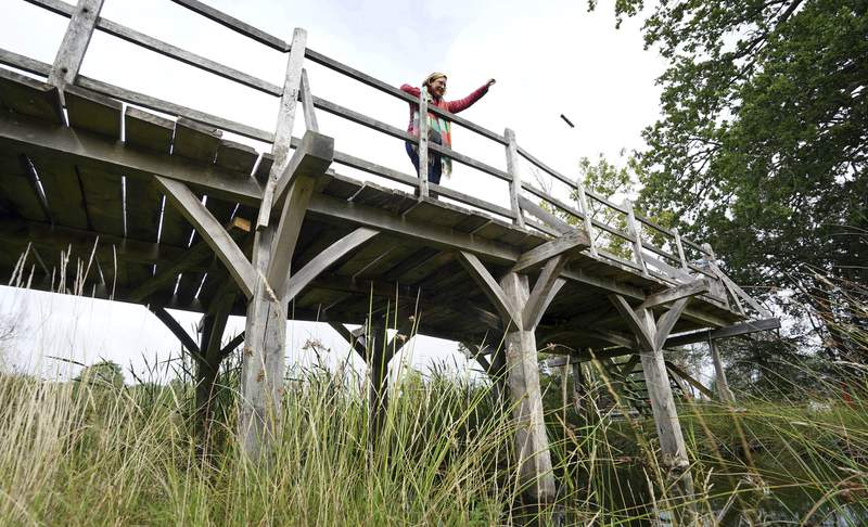 Silke Lohmann of Summers Place Auctions stands on the original Poohsticks Bridge from Ashdown Forest, featured in A.A. Milne's Winnie the Pooh books and E.H. Shepard's illustrations, near its original location in Tonbridge, Kent, England, Thursday, Sept. 30, 2021. The adventures of the honey-loving bear Winnie the Pooh have captivated children and their parents for nigh on 100 years. Fans now have a chance to own a central piece of Poohs history, when a countryside bridge from the south of England goes up for auction next week. The author of the hugely popular Pooh series of books, A. A. Milne, often played with his son, Christopher Robin, at the bridge in the 1920s. The bridge became a regular setting for the adventures of Pooh and his friends in the series that launched in 1926. The auctioneers have said theres been interest from around the world, but hoped that it stays local. (Gareth Fuller/PA via AP)
