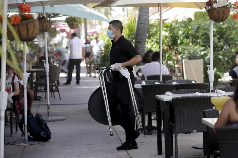 FILE - In this July 12, 2020, file photo, a waiter wears a protective face mask and gloves while working at the il bolognese restaurant along Ocean Drive during the coronavirus pandemic, in Miami Beach, Fla.  Wages and benefits for U.S. workers rose at the slowest pace in three years in the April-June quarter, a sign that businesses are holding back on pay as well as cutting jobs in the coronavirus recession.   (AP Photo/Lynne Sladky, File)