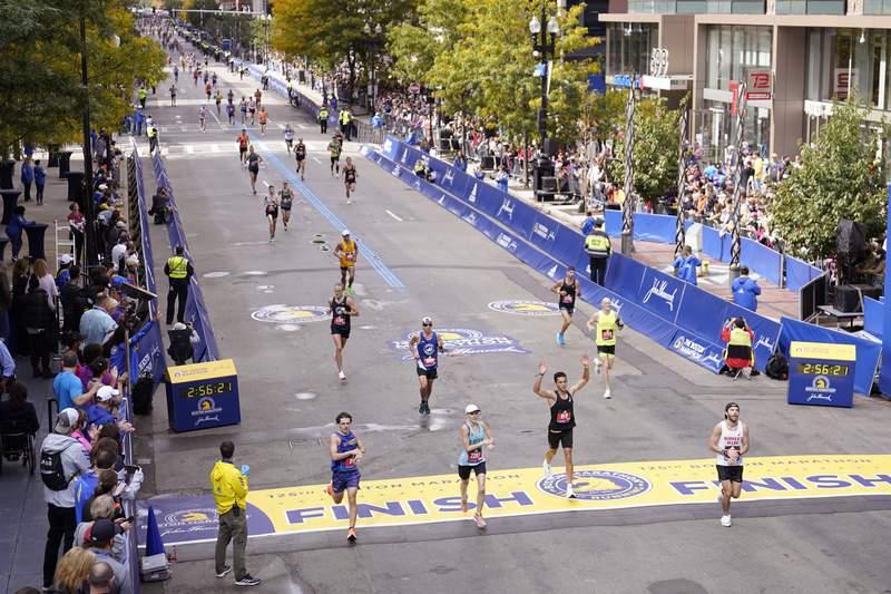 Runners cross the finish line at the Boston Marathon in Boston, on Monday, Oct. 11, 2021. (AP Photo/Charles Krupa)