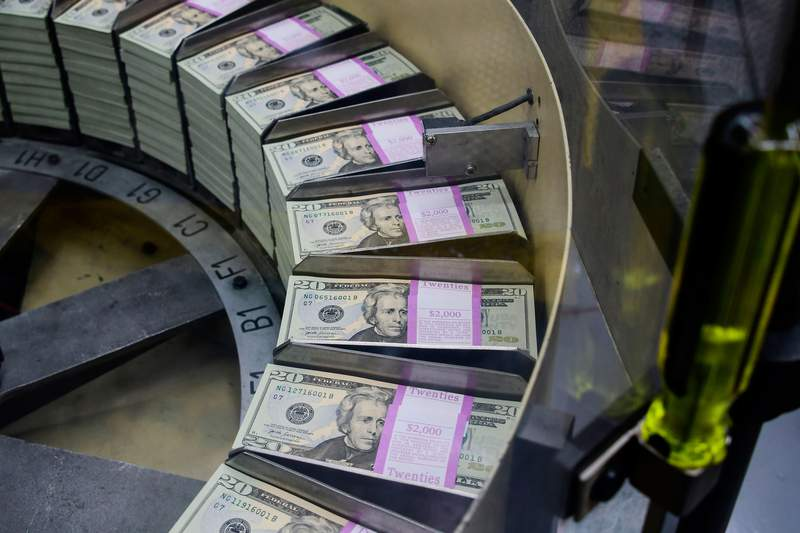 The US government is preparing to send out direct payments to help individuals amid the coronavirus pandemic, but those who need the money most may be waiting the longest to see it. Packs of freshly printed 20 USD notes are processed for bundling and packaging at the US Treasury's Bureau of Engraving and Printing in Washington, DC July 20, 2018.