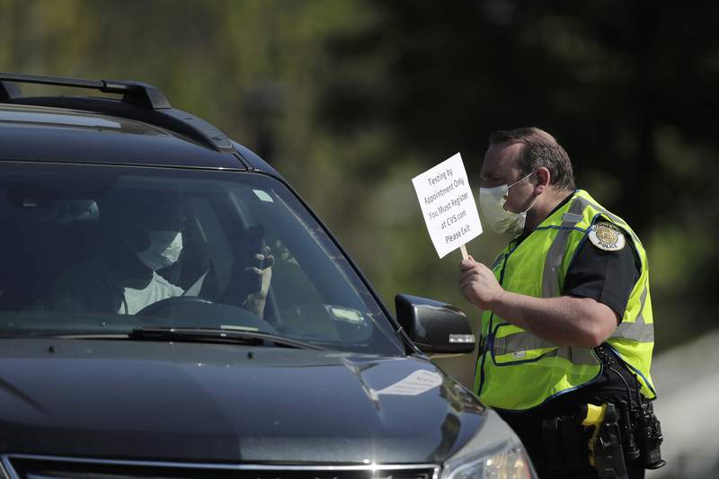 FILE - A person holds up their phone to show an official an appointment confirmation at a COVID-19 testing site on Georgia Tech's campus, Monday, April 6, 2020, in Atlanta. (AP Photo/Brynn Anderson)